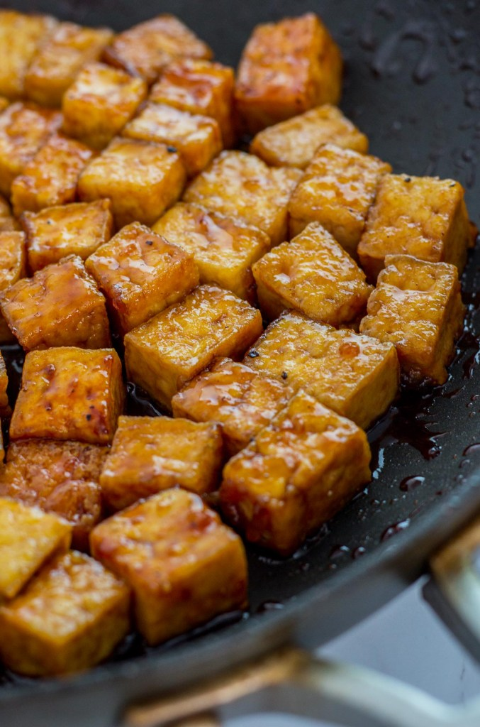 Close up shot of teriyaki tofu in the pan being simmered in the sauce