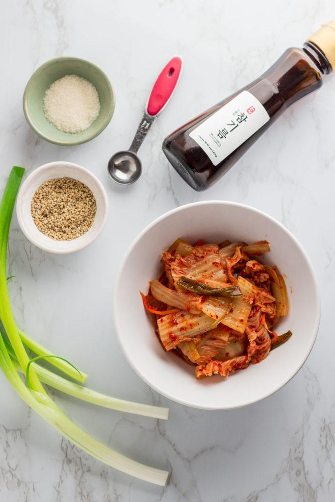 ingredients for stir fried kimchi - fermented kimchi, green onion, sesame seeds, sesame oil, and sugar