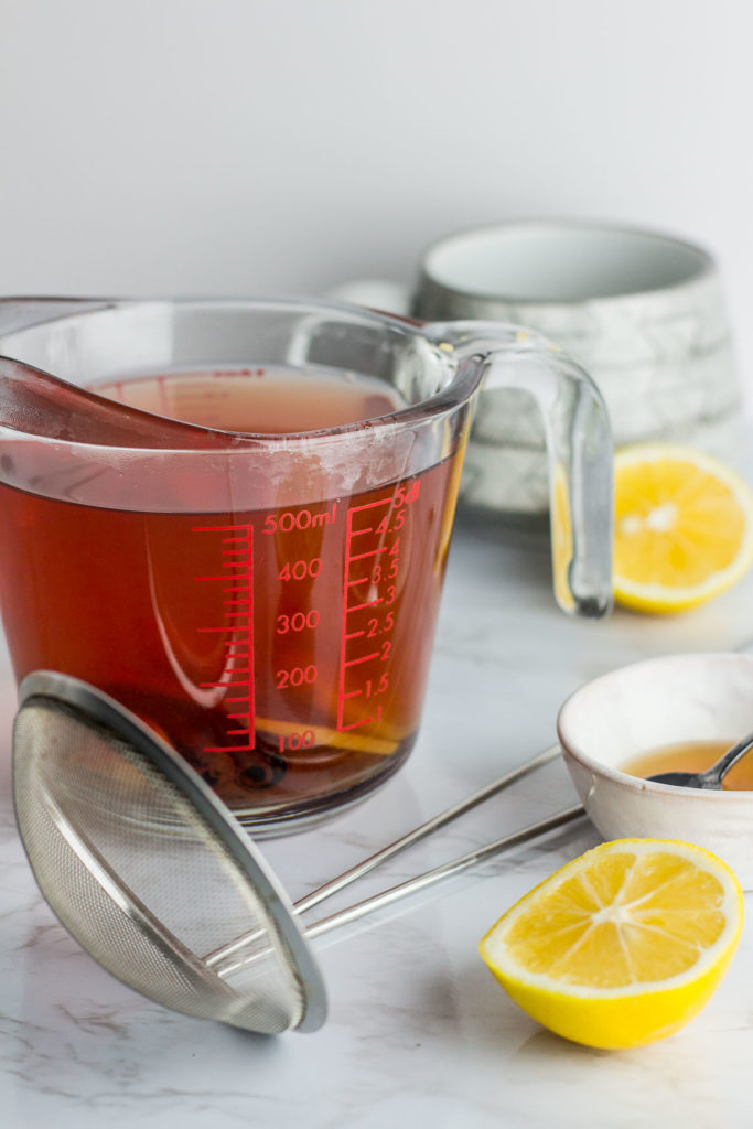 boiled ginger and cinnamon stick in the measuring cup with lemon and honey in the background