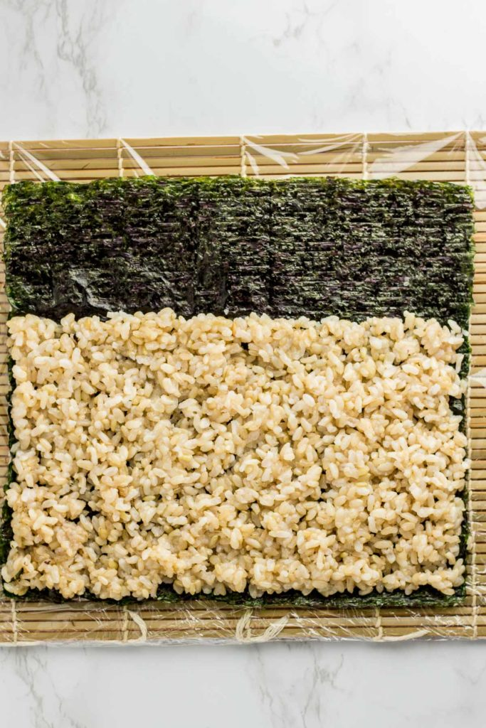 Rice is spread evenly on top of seaweed paper. Rice was not added to top part of the seaweed paper. About one third of the seaweed paper does not have rice.
