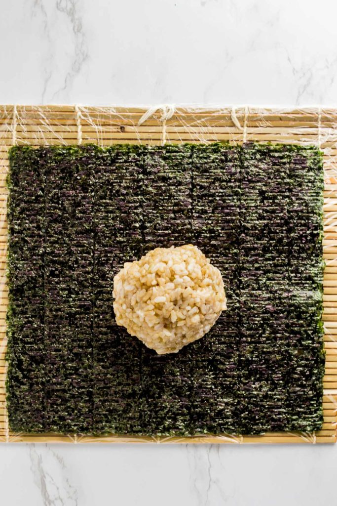 one cup of sushi rice on top of seaweed paper that is placed on top of wrapped sushi mat