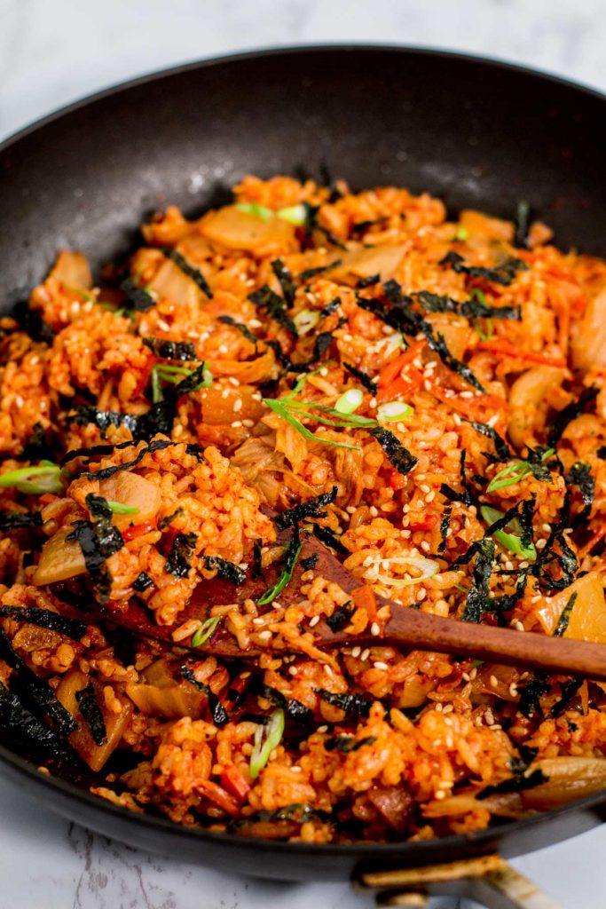 A pan full of kimchi fried rice with seaweed strips and sesame seeds on top as garnish