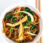 Overhead shot of japchae in a white bowl with chopsticks next to it