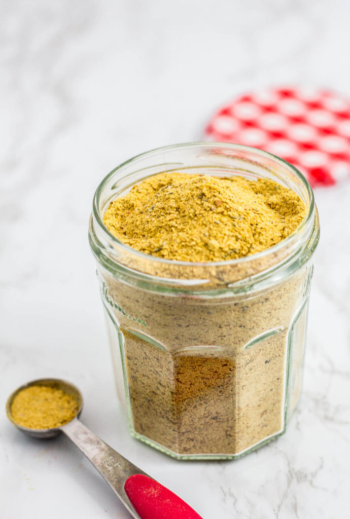 A clear jar full of chicken flavor bouillon powder with teaspoon in front