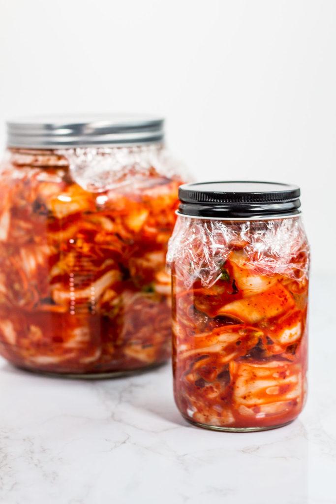 Glass jars of prepared homemade vegan kimchi, ready to be fermented