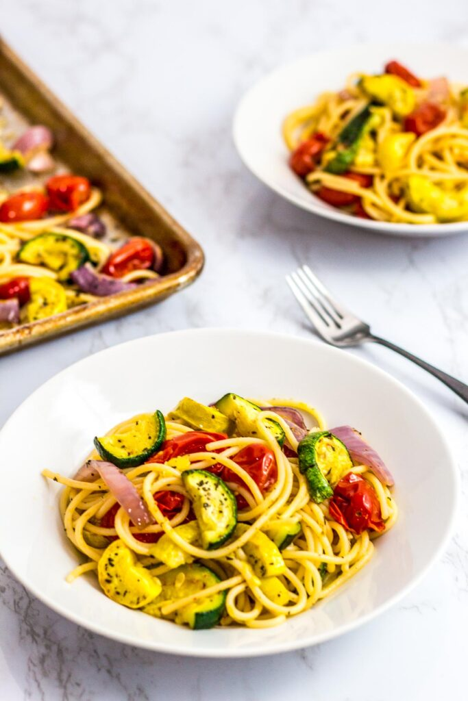 two plates of oven roasted summer veggie pasta with the sheet pan on the corner