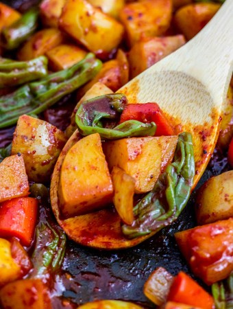 close up photo of spicy braised potatoes and shishito peppers on a wooden spoon
