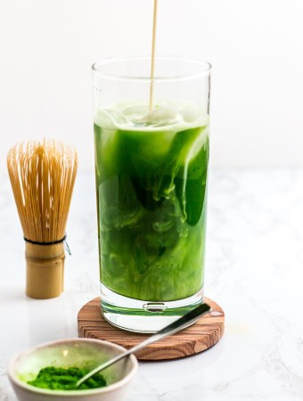 slow pouring of oat milk over iced matcha water