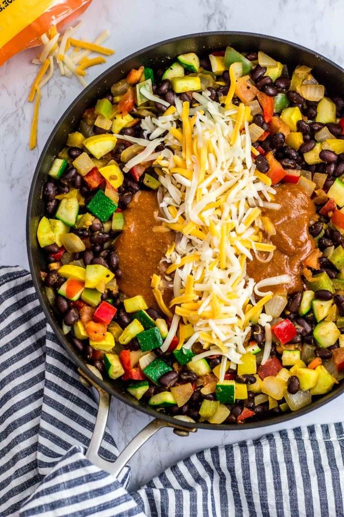 summer vegetables, red enchiladas sauce and shredded cheese filling for the enchiladas