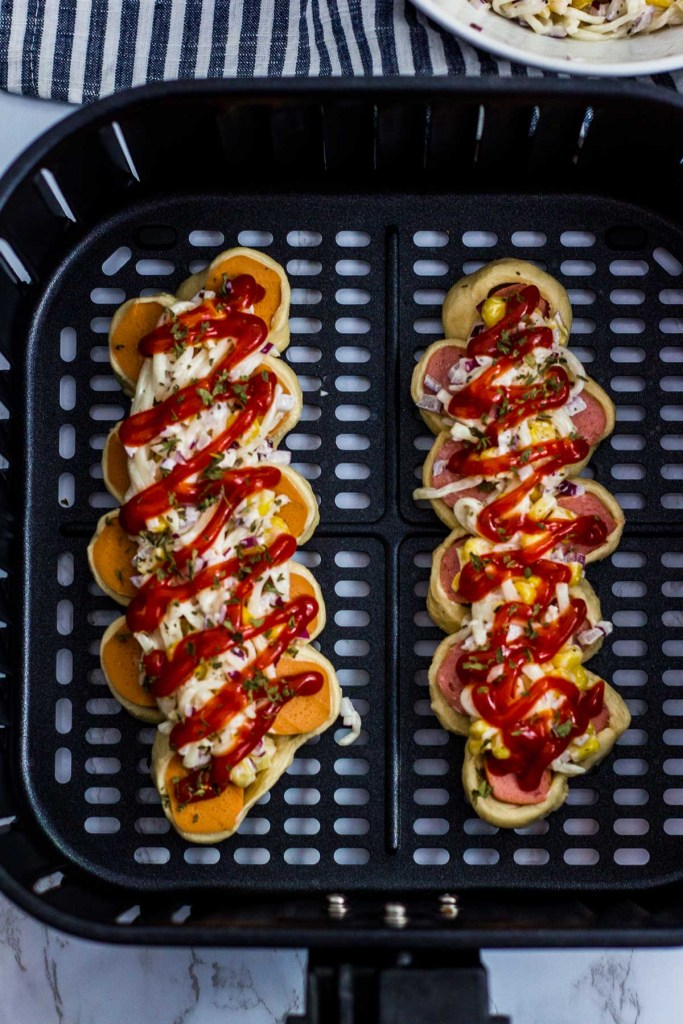 ketchup is drizzled on top of sausage bread before cooked in an air fryer