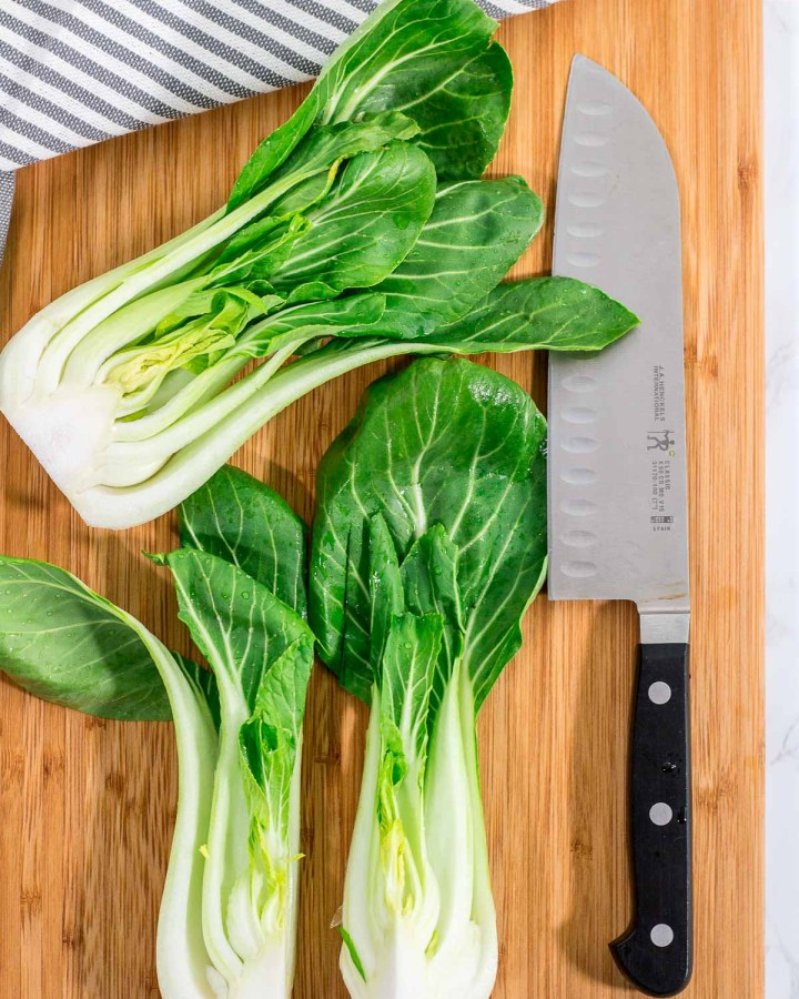 Bok choy cut in half and cut in half length wise again on the cutting board