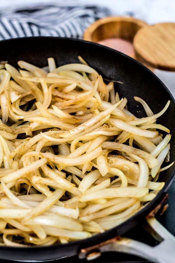 cooked sliced onion with brown sugar sprinkled on top