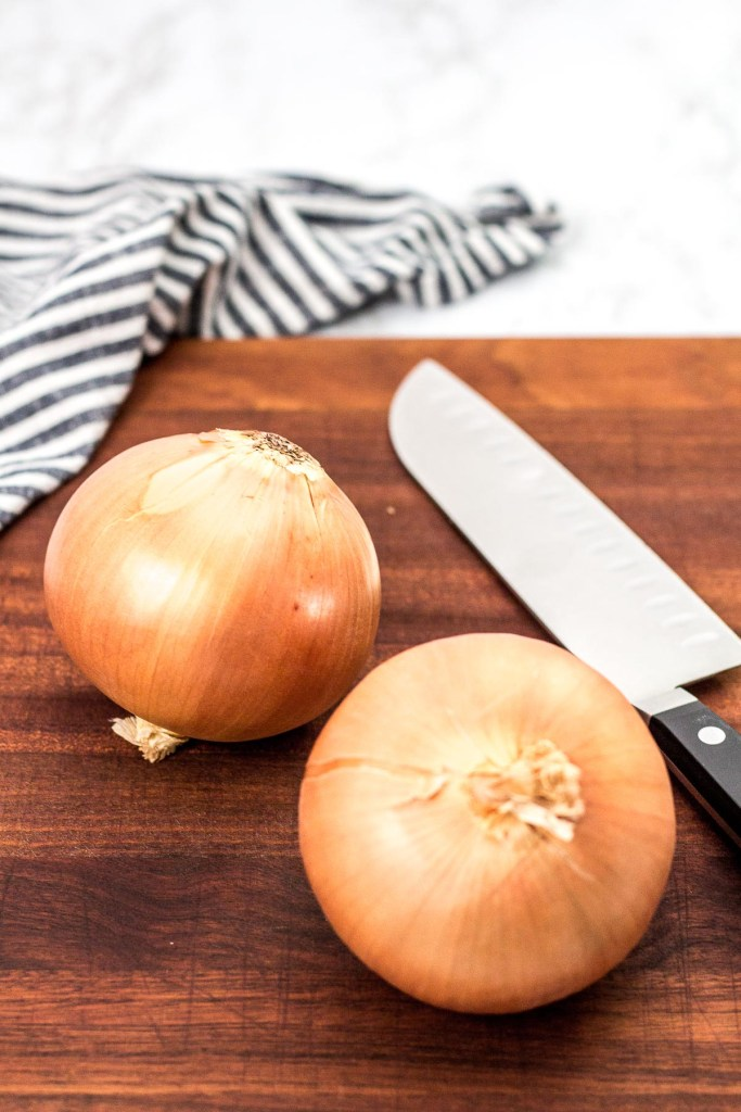 two large yellow onions on a cutting board with a chef knife