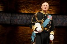 "This image released by The O + M Co. shows Tim Pigott-Smith during a performance of ""King Charles III,"" at the Music Box Theatre in New York. Pigott-Smith stars in Mike Bartlett's ""King Charles III,"" an ingenious view of what might happen when the Prince of Wales finally inherits the throne. It was the winner of the 2015 Olivier Award for Best New Play. (Joan Marcus/The O + M Co. via AP)"