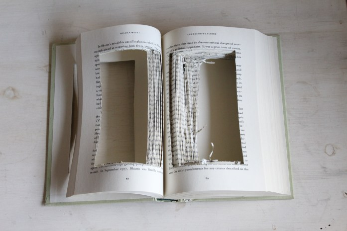 Step One: Carve out a rectangle in the middle of your book with an x-acto knife. Step Two: Glue pages together with spray adhesive. Step Three: Line the inside of the edges with a plastic container. Cut to fit. Step Four: Layer bottom with rocks, then soil, plant succulents and top off with decorative rocks.