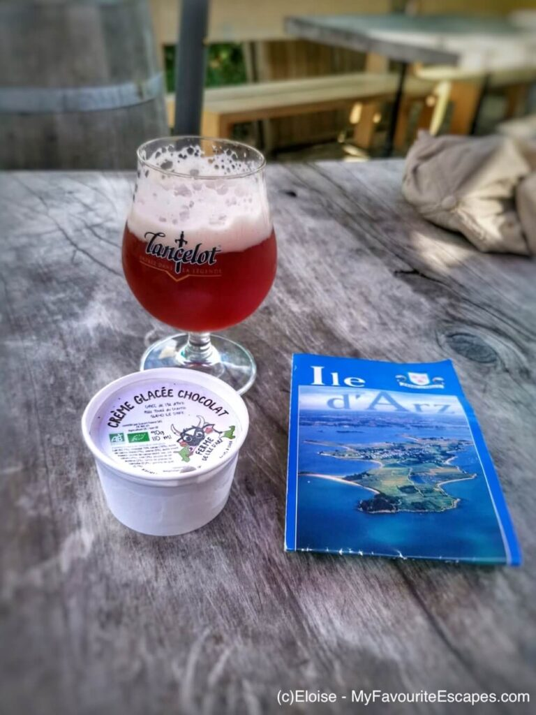 A beer, an ice cream and a map of the Isle of Arz all next to each others on a table at a cafe.