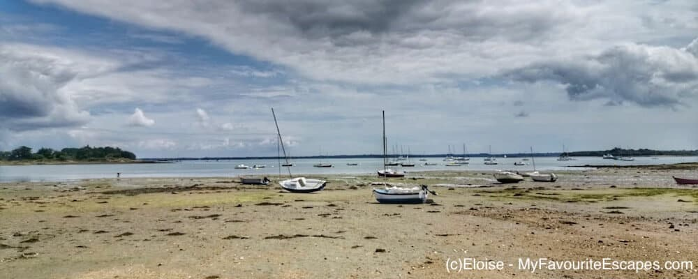 A beach at low tide on the Ile d'Arz with boats on the sand.