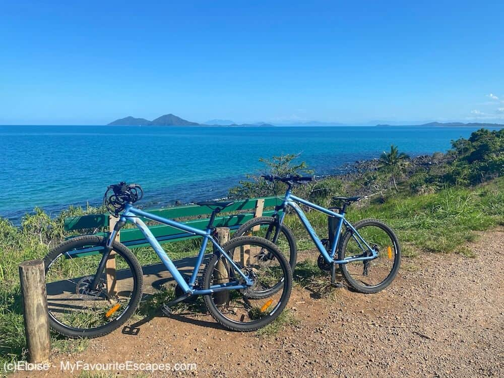 Two rental bikes parked against a bench with a view of the ocean and Dunk Island in the background