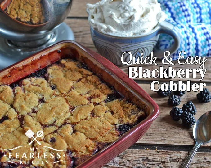 blackberry cobbler in a stoneware dish with homemade whipped cream