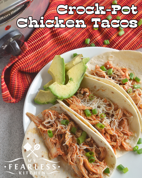 three soft-shell chicken tacos with a slow cooker and red placemat in the background