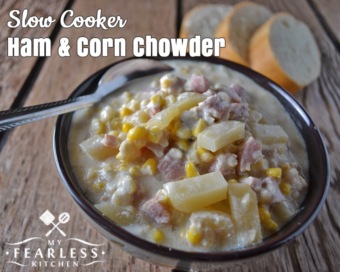 bowl of slow cooker ham and corn chowder with bread in the background