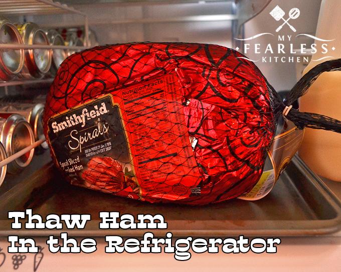 frozen spiral-sliced ham thawing in a refrigerator