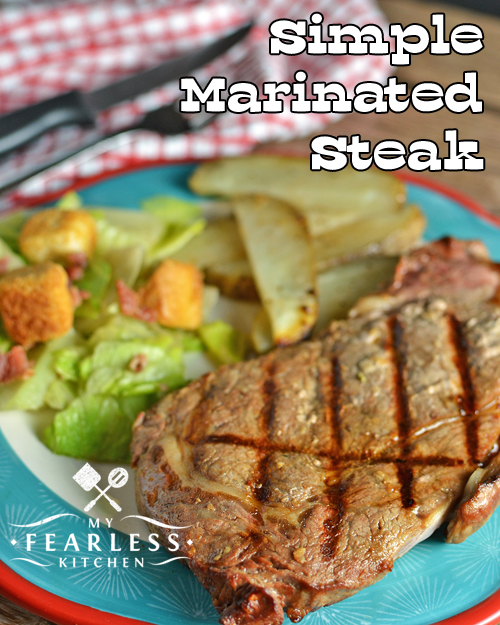 grilled, marinated ribeye steak on a plate with salad and potatoes