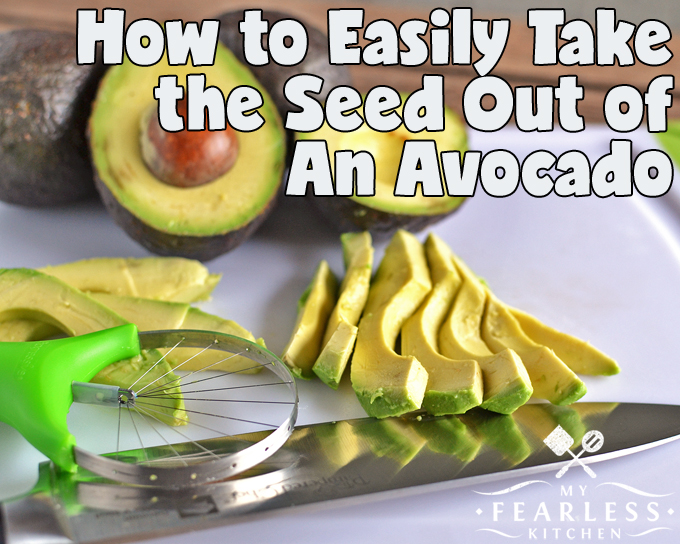 sliced avocado on a cutting board with a knife, avocado slicer, and more avocados in the background