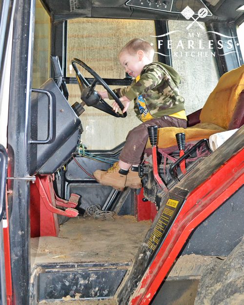 little boy pretending to drive a big tractor