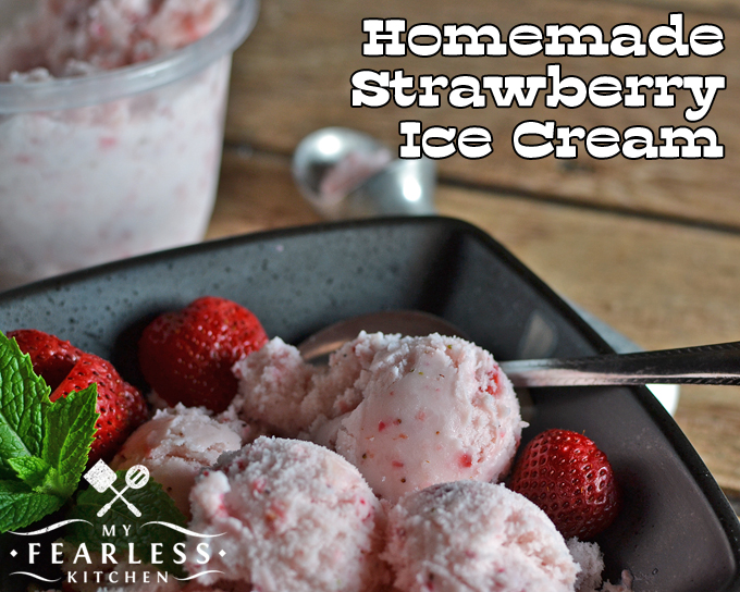 three scoops of homemade strawberry ice cream in a dark bowl with fresh strawberries and mint