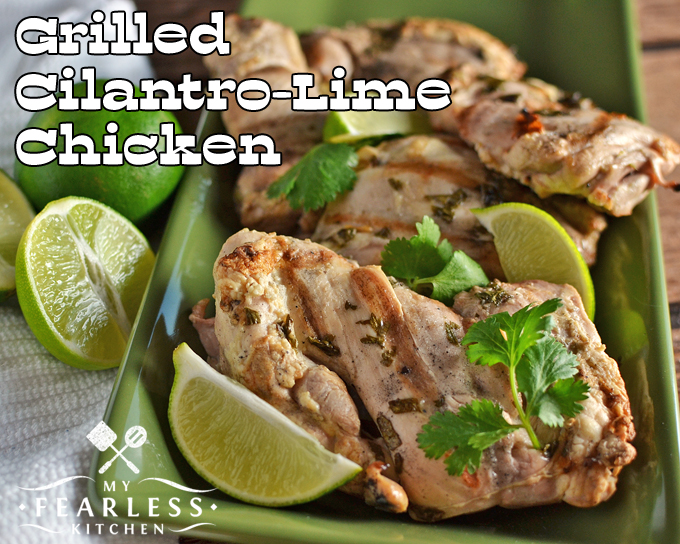 grilled cilantro-lime chicken on a green plate with limes and cilantro garnish