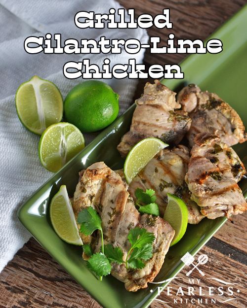 grilled cilantro-lime chicken thighs on a green tray with limes and cilantro
