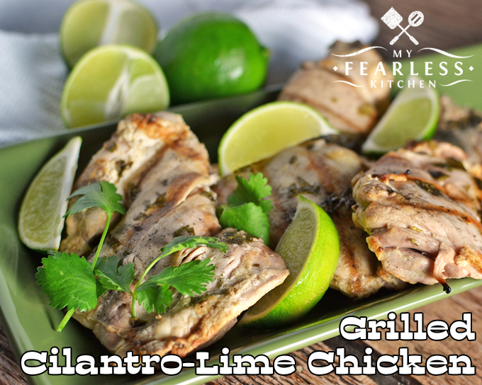 close-up view of grilled cilantro-lime chicken with limes in the background