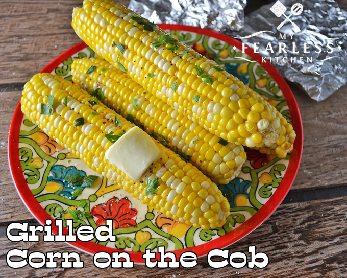 a plate of sweet corn on the cob on a wooded background