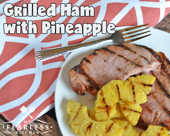 grilled ham with pineapple slices on a white plate with an orange and white placemat