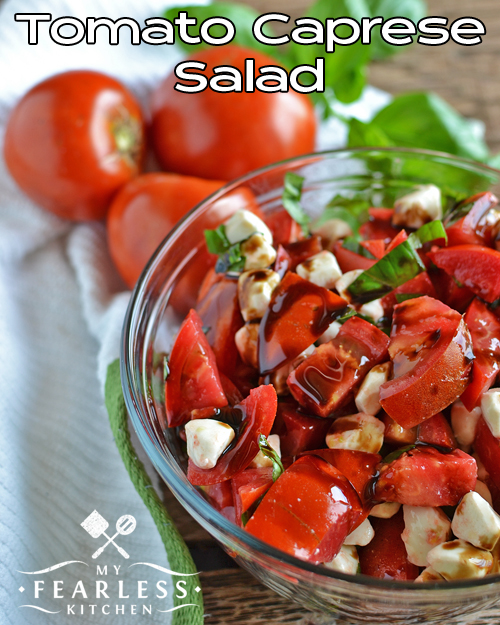a large bowl of tomato caprese salad with more fresh tomatoes and fresh basil in the background