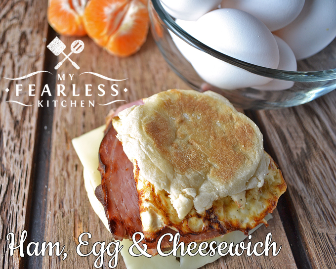 close up view of a ham, egg, and cheese breakfast sandwich on a wood background