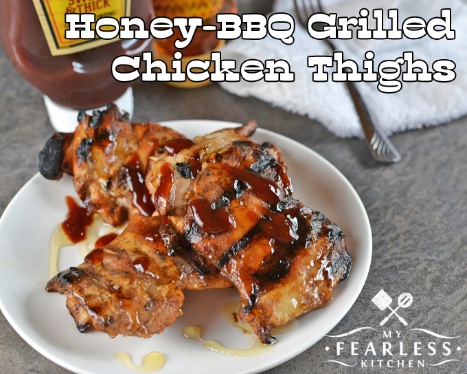 honey-bbq grilled chicken thighs on a white plate with extra sauce