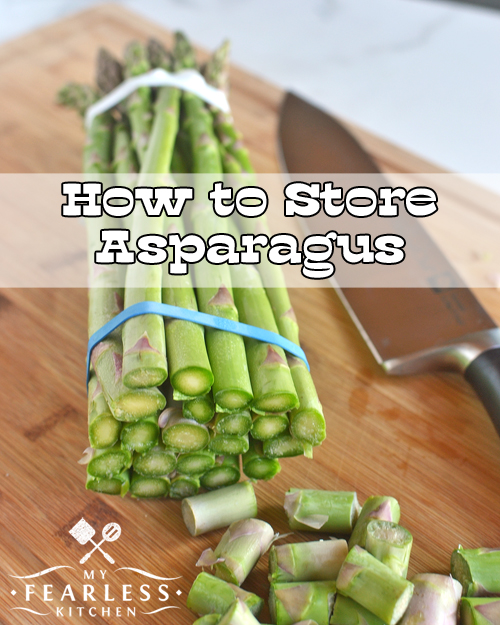 freshly cut asparagus spears with a knife on a wooden cutting board