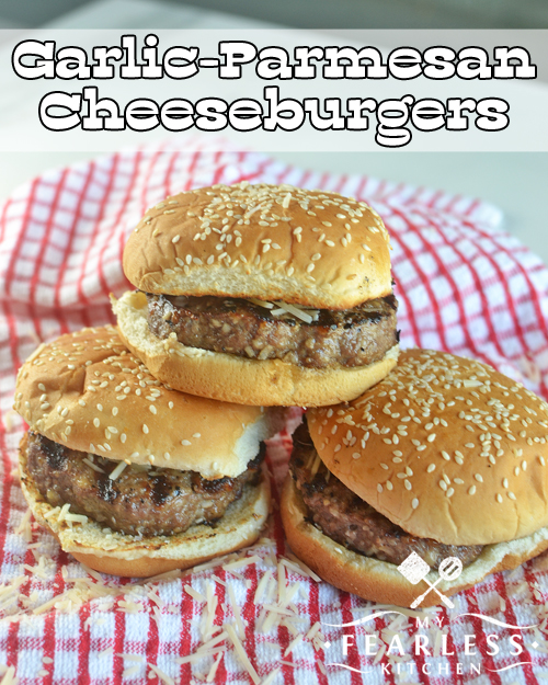 three garlic-parmesan cheeseburgers with sesame seed buns on a red and white plaid napkin