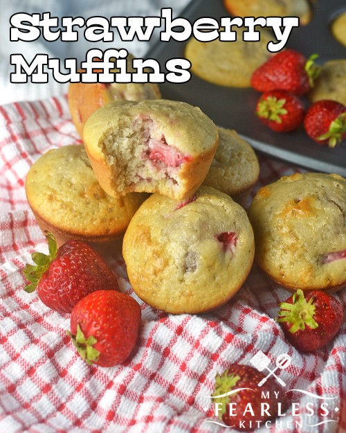 a pile of strawberry muffins with fresh strawberries on a red and white checked napkin; one of the muffins has a bite taken out