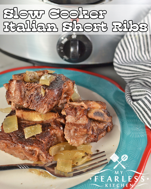 Slow Cooked Italian Short Ribs with onions on a plate in front of a slow cooker