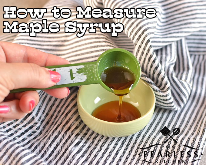 a hand holding a measuring spoon with maple syrup
