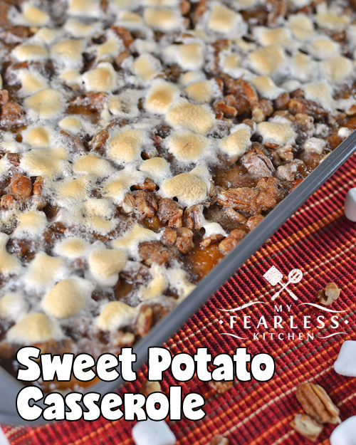 sweet potato casserole with marshmallows and pecans on a red and orange tablecloth