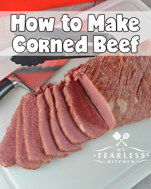 sliced corned beef with a chef's knife and tongs on a white cutting board