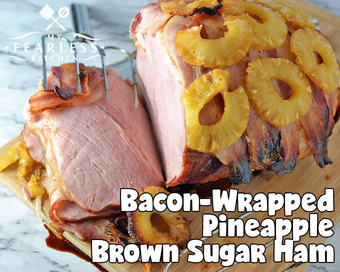 boneless ham wrapped with bacon and layered with pineapple slices on a wooden cutting board