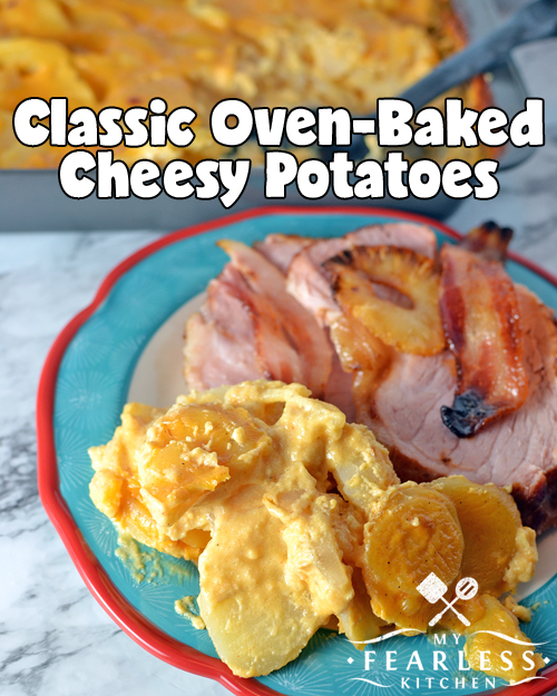 cheesy potatoes on a plate with a thick slice of ham with a casserole dish full of more potatoes in the background