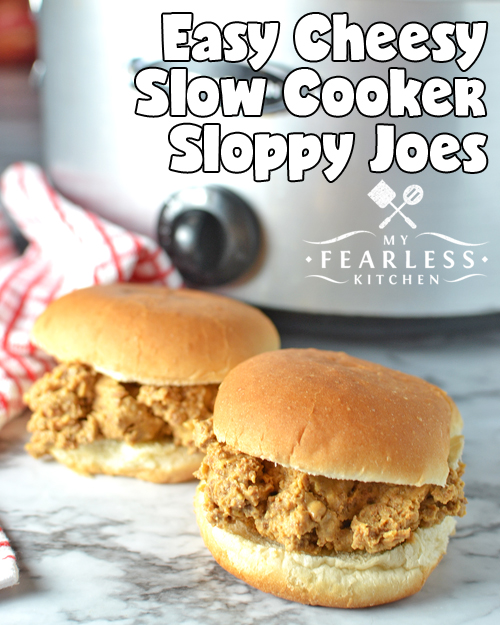 two cheesy slow cooker sloppy joes with a slow cooker in the background