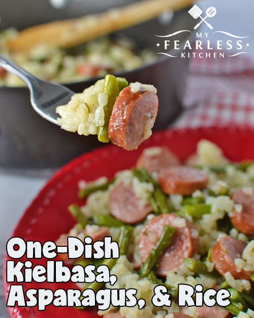 A fork with sliced kielbasa, asparagus pieces, and creamy short-grain rice
