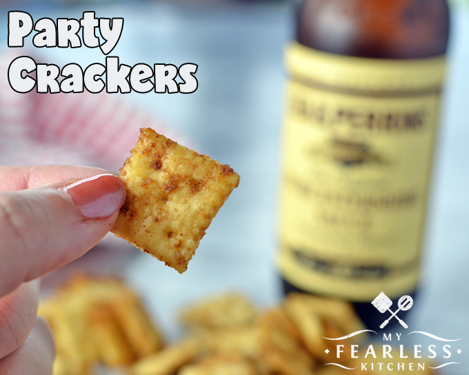 a hand holding a seasoned mini party cracker with more crackers and a bottle of worcestershire sauce in the background